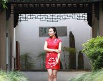 Chinesischer cheongsam Modellstand nahe bei Bonsais Stockbild