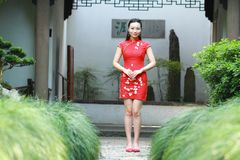 Chinesischer cheongsam Modellstand nahe bei Bonsais Lizenzfreie Stockfotos