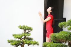 Chinesischer cheongsam Modellstand nahe bei Bonsais Stockfoto