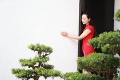 Chinesischer cheongsam Modellstand nahe bei Bonsais Lizenzfreies Stockbild