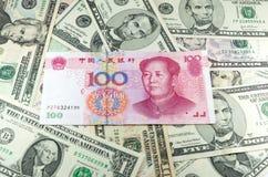 Chinesischer CNY-Yuan auf Hintergrund vieler Dollar Lizenzfreie Stockfotografie