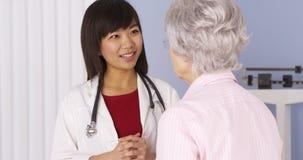 Chinesischer Doktor, der älteren Patienten konsultiert stockbilder