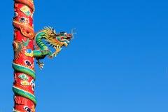 Chinesischer Drache auf der roten Säule lokalisiert auf blauer Himmel-Hintergrund Stockfotos