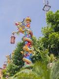 Chinesischer Drache um rote Spalte im blauen Himmel Stockfotografie