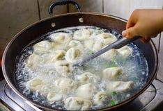 Chinesischer Familien-Koch Boilded Dumplings in einem Wok Lizenzfreie Stockfotos