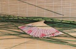 Chinesischer Fan, der auf Bambusmatte im Grün liegt lizenzfreies stockbild