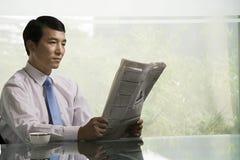 Chinesischer Geschäftsmann, der eine Zeitung liest lizenzfreie stockbilder
