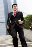 Chinesischer Geschäftsmann, der hinunter Jobstepps hetzt lizenzfreies stockfoto