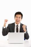 Chinesischer Geschäftsmann, der an Laptop und Celebra arbeitet Stockfoto