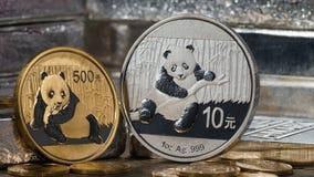 Chinesischer Goldpanda gegen Silberner Panda mit Silberbarren Lizenzfreie Stockfotos