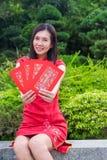 Chinesischer Gruß des neuen Jahres mit Cheongsam und roten peckets Stockfotos