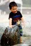 Chinesischer Junge, der mit Wasser spielt Lizenzfreie Stockfotografie