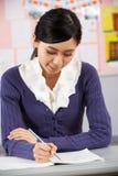 Chinesischer Lehrer, der am Schreibtisch im Klassenzimmer sitzt stockfoto