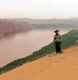Chinesischer Mann, der geht, den Sandhügel in der Bank von Gelbem Fluss Huang He unten zu schieben Stockfotografie