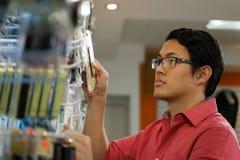 Chinesischer Mann, der Usb-Antrieb auf Regal im Computer-Shop bestellt Stockbilder