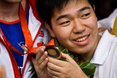 Chinesischer Mann hält olympische Medaille an Lizenzfreies Stockfoto