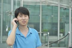 Chinesischer Mann mit seinem Handy Lizenzfreie Stockfotografie