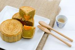 Chinesischer Mondkuchen auf weißer Platte mit Schale heißem Tee Stockbild