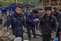 Chinesischer Polizist auf einer ländlichen Feier essend unter Verwendung des hölzernen cho Stockbilder