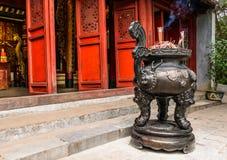 Chinesischer Räucherstäbchentopf vor roter Tür des chinesischen Tempels herein Stockfoto
