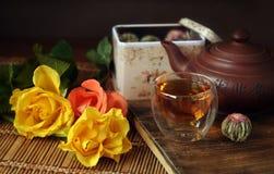 Chinesischer Tee, keramische Teekanne, Glasteeschale und gelbe Rosen Nahaufnahme Stockfoto