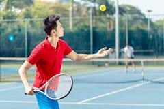 Chinesischer Tennisspieler bereit, den Ball beim Dienen zu schlagen in einem Tennismatch Stockfotografie