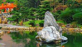 Chinesischer Zengarten mit roter Brücke und Felsen Stockfotografie