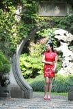 Chinesisches cheongsam Modell im chinesischen klassischen Garten, der mitten in schönem Tor an Qiyuan-Garten steht Lizenzfreie Stockfotos