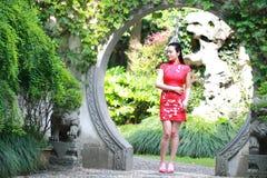 Chinesisches cheongsam Modell im chinesischen klassischen Garten, der mitten in schönem Tor an Qiyuan-Garten steht Lizenzfreies Stockfoto