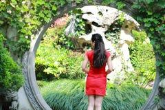 Chinesisches cheongsam Modell im chinesischen klassischen Garten, der mitten in schönem Tor an Qiyuan-Garten steht Stockfotos