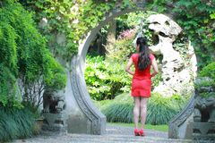 Chinesisches cheongsam Modell im chinesischen klassischen Garten, der mitten in schönem Tor an Qiyuan-Garten steht Lizenzfreies Stockbild