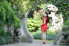 Chinesisches cheongsam Modell im chinesischen klassischen Garten, der mitten in schönem Tor an Qiyuan-Garten steht Stockbilder