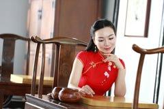 Chinesisches cheongsam Modell im chinesischen klassischen Garten sitzen auf einem Schemelspiel gehen Stockfotografie