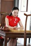 Chinesisches cheongsam Modell im chinesischen klassischen Garten sitzen auf einem Schemelspiel gehen Lizenzfreie Stockbilder