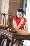 Chinesisches cheongsam Modell im chinesischen klassischen Garten sitzen auf einem Schemelspiel gehen Stockfotos