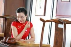 Chinesisches cheongsam Modell im chinesischen klassischen Garten sitzen auf einem Schemelspiel gehen Lizenzfreies Stockbild