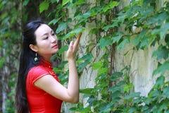 Chinesisches cheongsam Modellspiel in einem berühmten Garten Stockbild