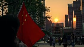 Chinesisches fahnenschwenkendes der Zeitlupe und Schlag im Wind mit Sonnenuntergang an einer Straße stock video