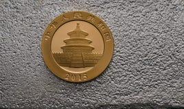 Chinesisches Gold Panda Coin auf Silberbarren Stockbild