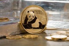 Chinesisches Gold Panda Coin mit Silberbarren im Hintergrund Stockbild
