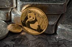 Chinesisches Gold Panda Coin vor Silberbarren auf Karte Stockbild