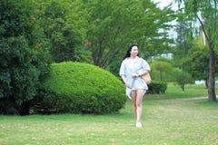 Chinesisches junges attraktives Studentenmädchen mit dem langen Haar, das in tragendem Buch des Campusgrün-Parks aufwirft stockfotos