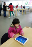 Chinesisches Kind, das ipad im Apfelspeicher spielt Stockbild