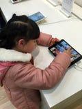 Chinesisches Kind, das ipad spielt Stockbild