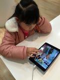 Chinesisches Kind, das ipad spielt Stockfoto