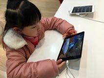 Chinesisches Kind, das ipad spielt Stockbilder