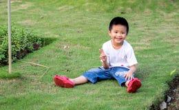 Chinesisches Kind (Junge) sitzen auf dem Gras Stockbilder
