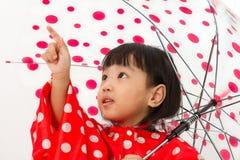 Chinesisches kleines Mädchen, das Regenschirm mit Regenmantel hält Stockbilder