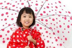 Chinesisches kleines Mädchen, das Regenschirm mit Regenmantel hält Lizenzfreies Stockbild