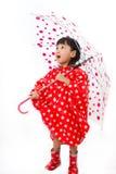 Chinesisches kleines Mädchen, das Regenschirm mit Regenmantel hält Stockbild